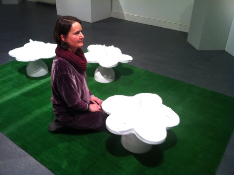 Jo Shapcott posing for press shots with Helen Chadwick's 'Piss Flowers' at the opening of Transformation.